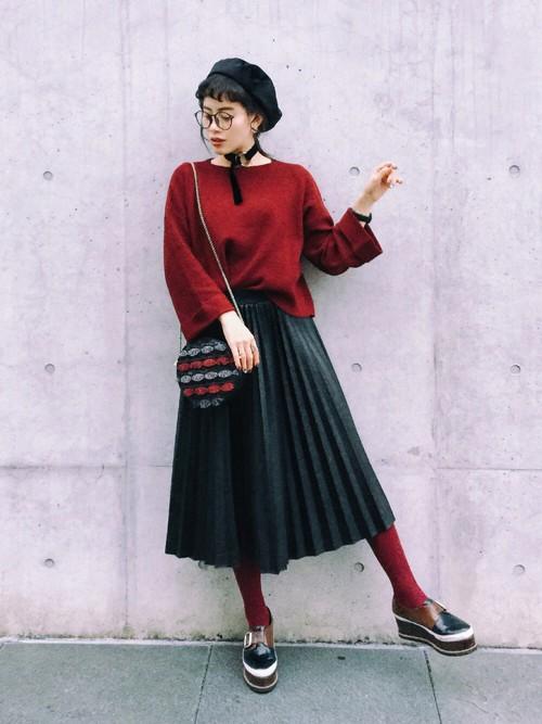 ボルドーのニットを黒のプリーツスカートにタックインしてプラットホームシューズを履いた女性