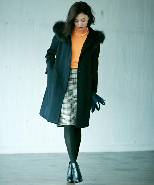 黒のファーコートにオレンジのニットと千鳥格子スカートを合わせたコーデ