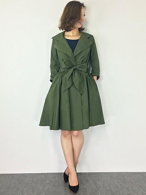 リボンのウエストマークがあるグリーンのテロンチを着た女性