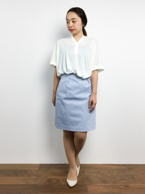 白のブラウスにブルーのスカートを履いた女性