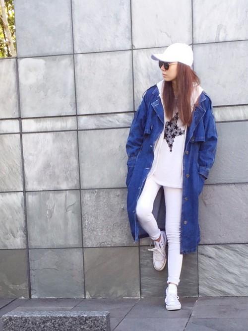 白のキャップにロングデニムジャケットの女性