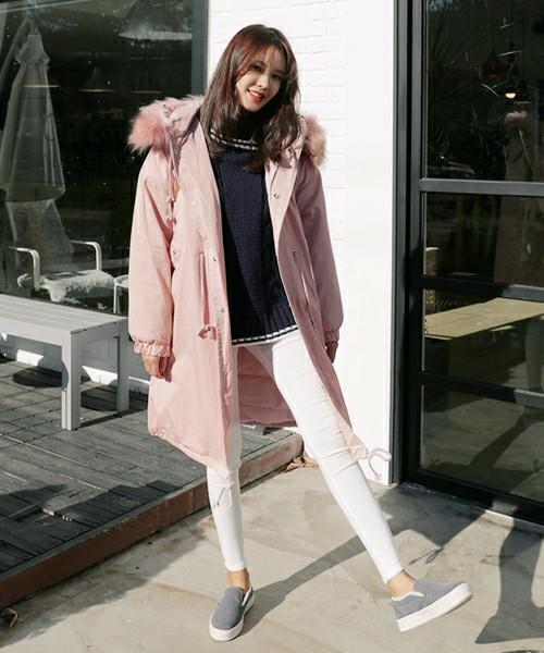 白パンツにピンクのモッズコートの女性