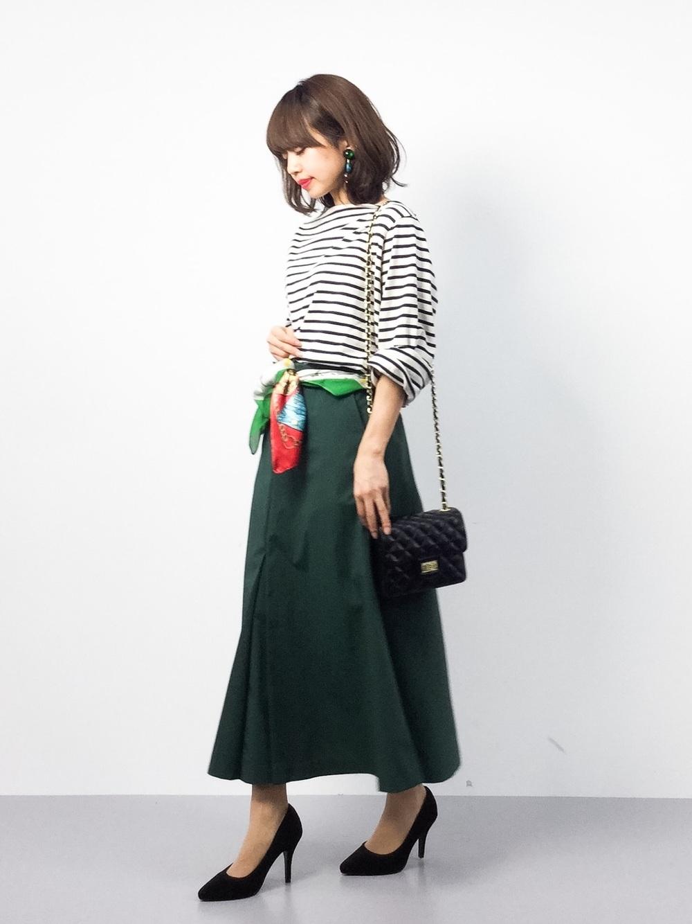 緑のフレアスカートにボーダートップスをきてウエストにスカーフを巻いて下をむいている女性