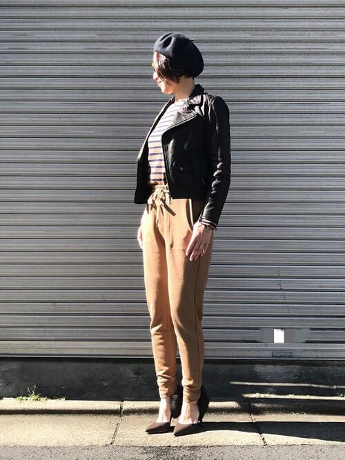 キャメルのジョガーパンツにボーダーのカット、ライダースを羽織った女性