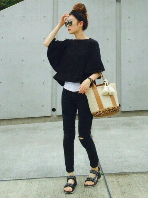 黒トップスと黒スキニーを着た女性