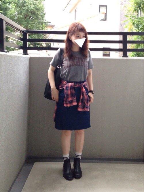 チャコールのTシャツにデニムスカートを履いた女性