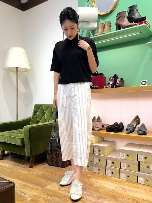 黒のトップスに白いストライプパンツを履き、グレーの靴を履いた女性