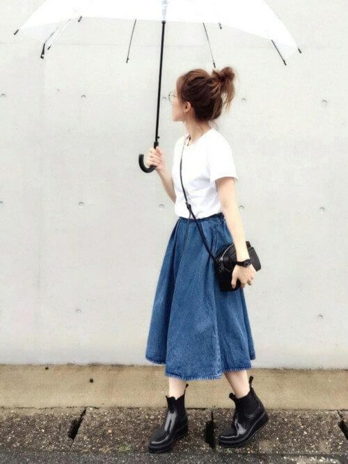 白いTシャツにデニムスカートを履き、傘を持った女性