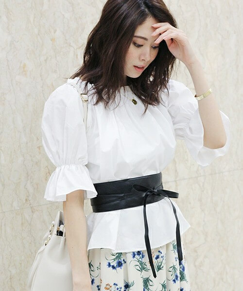 白い袖コンシャスなブラウスに花柄ボトムスを履きサッシュベルトをした女性