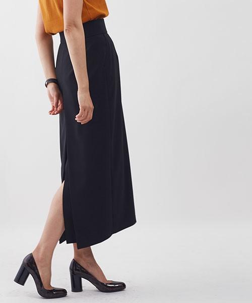 黒のロング丈バックスリットスカートをはきパンプスをはいて立つ女性