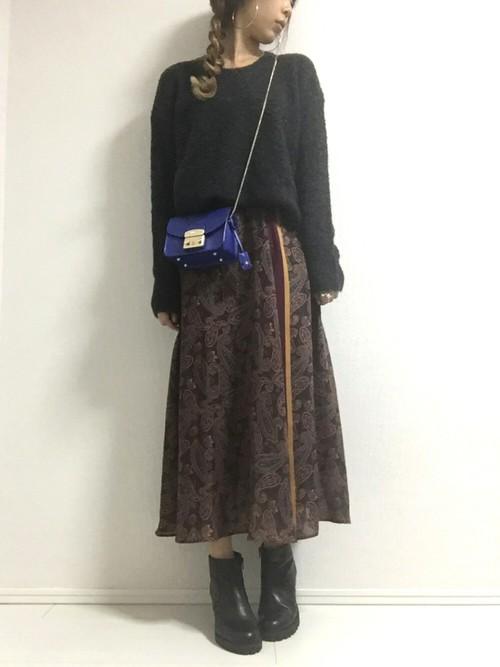 黒のニットに茶色のスリットスカートと黒のブーツをはいて立つ女性
