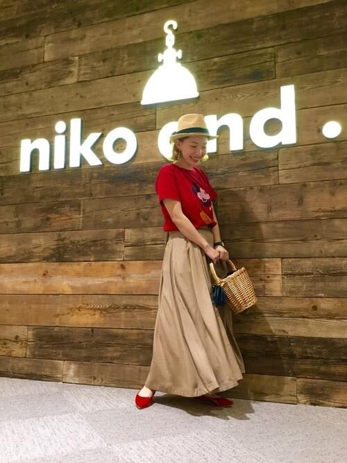 赤のTシャツにチノフレアスカートで、赤いぺたんこ靴を履いた女性