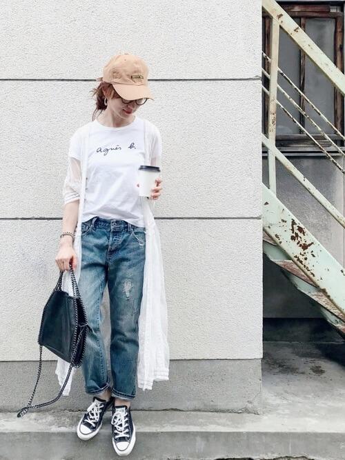 白Tシャツ、デニムパンツにガウンを合わせスニーカーを履いた女性