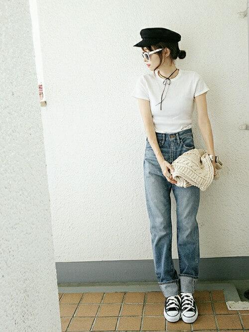 白のTシャツにジーンズとスニーカーをはいて黒のチョーカーをつけて立つ女性
