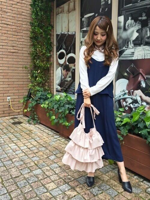 スカーフ風のチョーカーをつけ紺のオールインワンを着てピンクのフリルバッグを持ち立つ女性