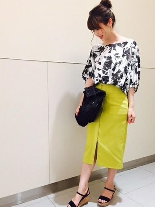 黒い花柄の白のトップスに黄色のスリットスカートの女性