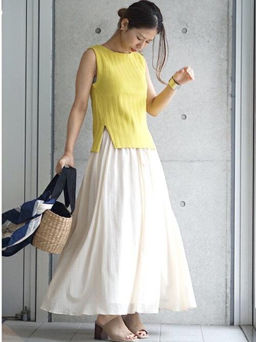 黄色のノースリーブリブニットに白のロングスカートの女性