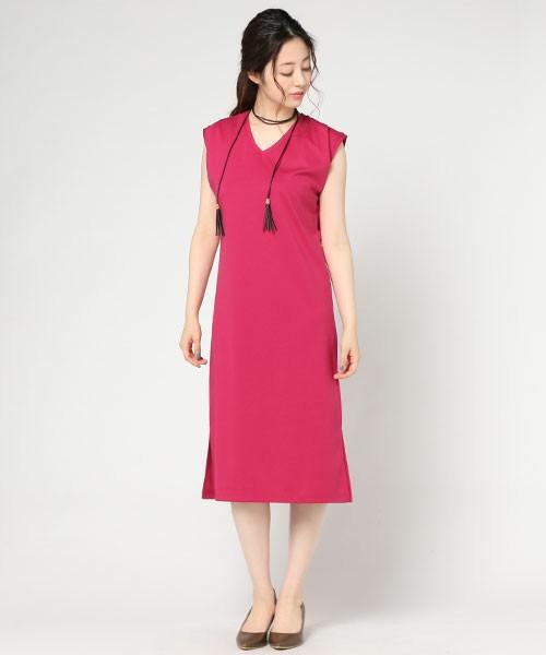 濃いピンクのVネックワンピースにラリエットをつけて立つ女性