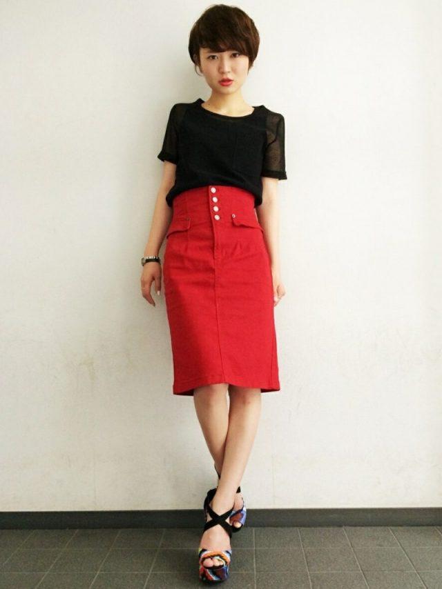 黒トップスにデニムの赤スカートの女性