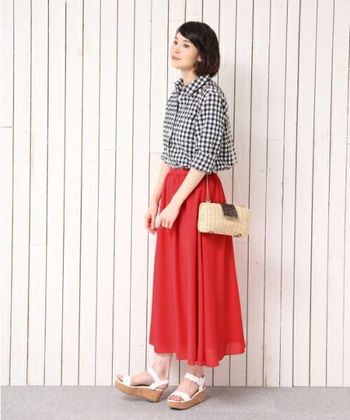 チェック柄シャツに赤スカートの女性
