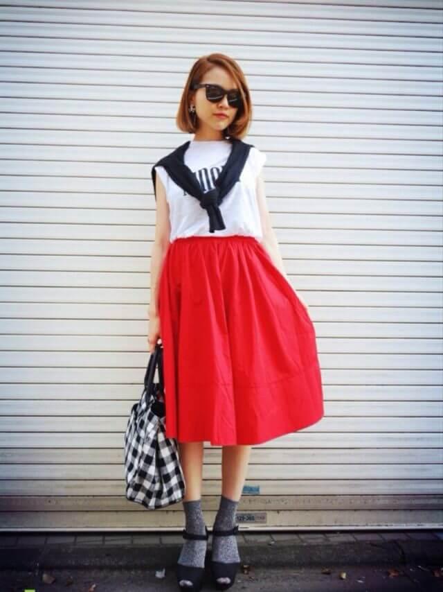白Tシャツに赤スカートの女性