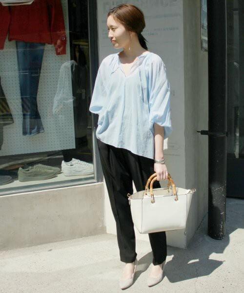 水色の透けトップスにネイビーのパンツを合わせた女性