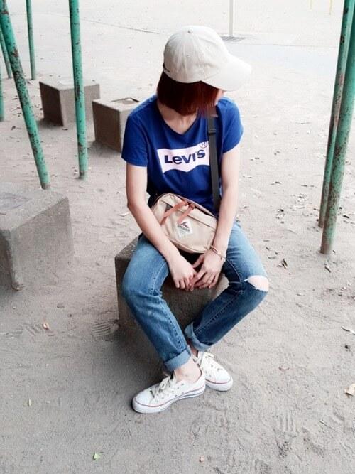 ネイビーのLevi's Tシャツにデニムパンツを履いた女性