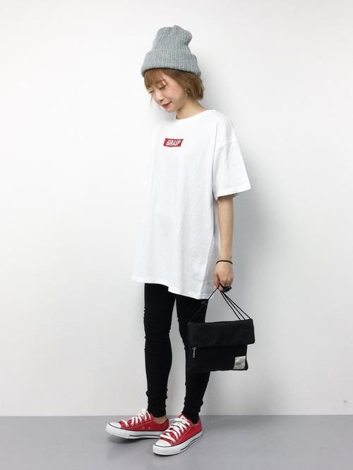 白いロゴTシャツに黒いジョガーパンツを履いてニットをかぶった女性