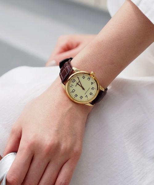 クロコ調ベルトのチープカシオの腕時計をした女性の手