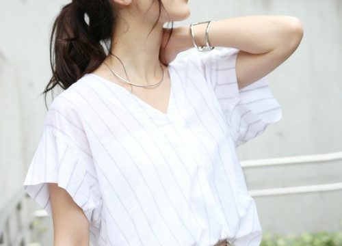 白地にストライプの半袖シャツにベージュのボトムスを履いた女性