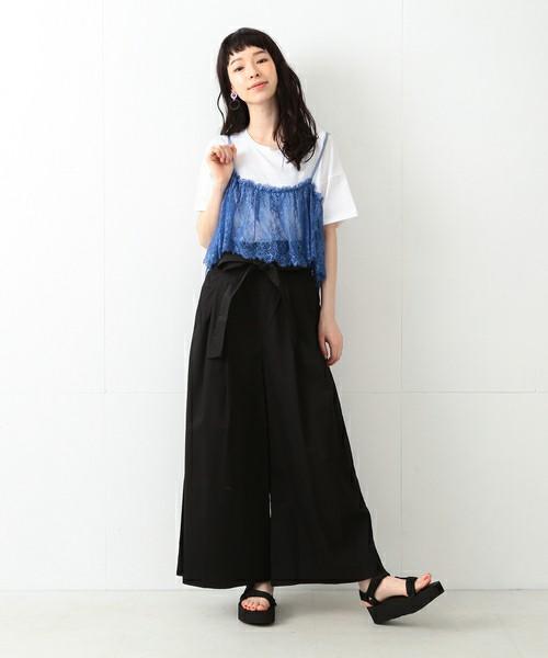 白Tにブルーのキャミをレイヤードし黒いワイドパンツを履いた女性