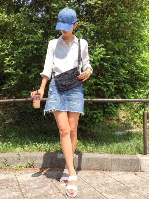 白のシャツにデニムミニスカートを履いた女性