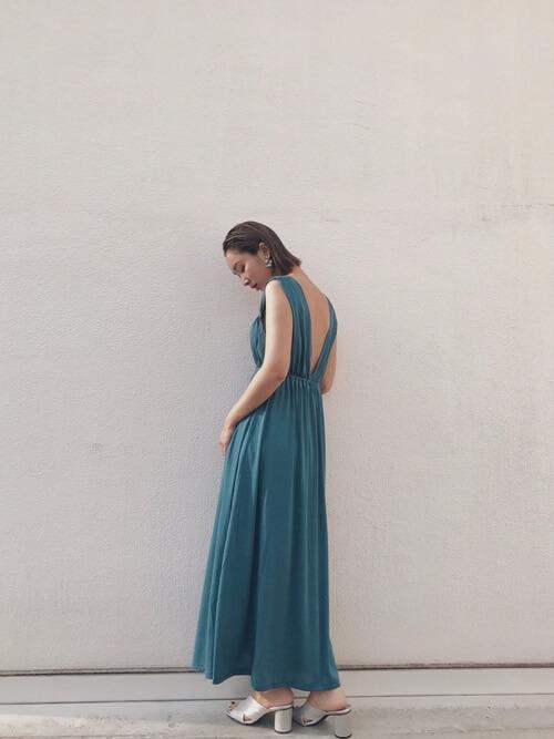 ブルーの背中開きワンピースを着る女性