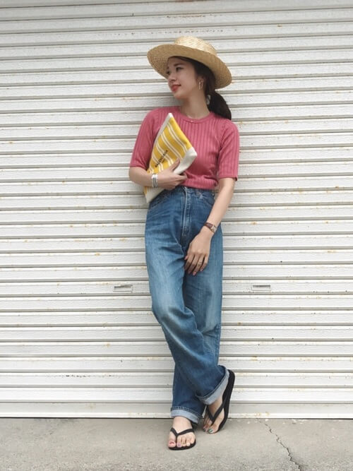ピンクのリブTにハイウエストのデニムパンツを履いた女性