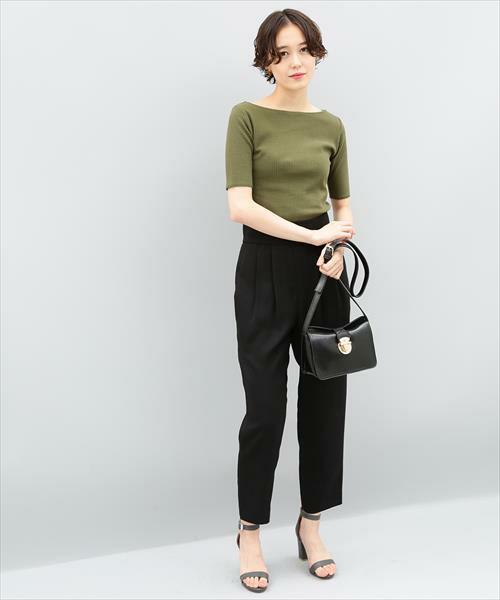 カーキのリブTに黒のタックパンツを履いた女性