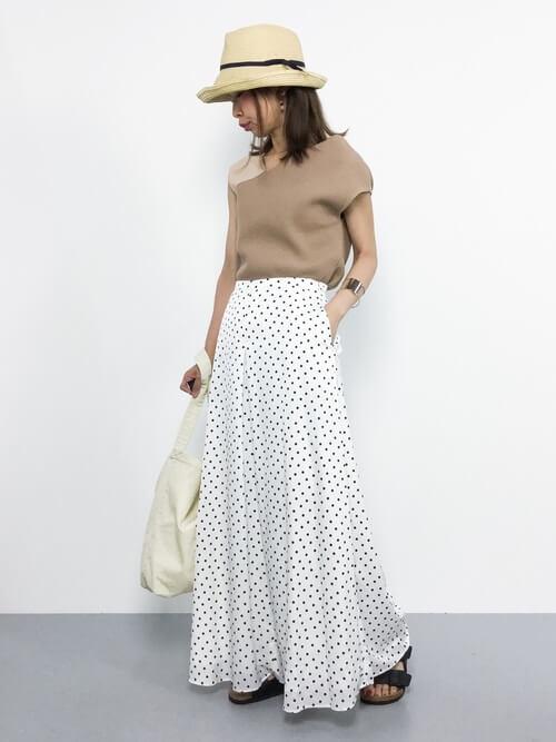 ベージュのトップスにドットのロングスカートを合わせる女性