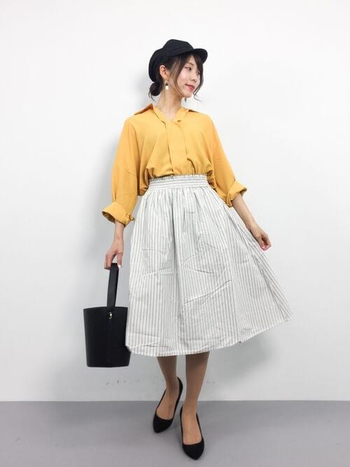 黄色シャツに白いストライプスカート
