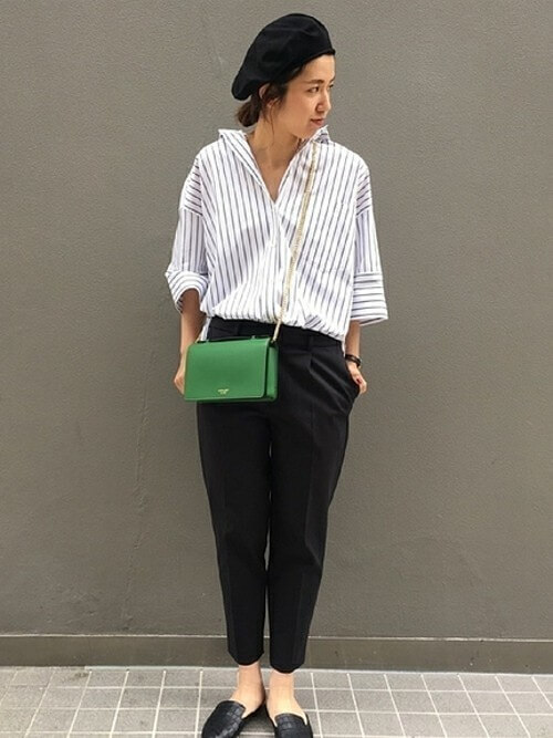 ストライプのシャツに黒のパンツを履いた女性
