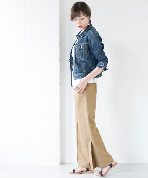 デニムジャケットにベージュのサイドスリットパンツを履いた女性