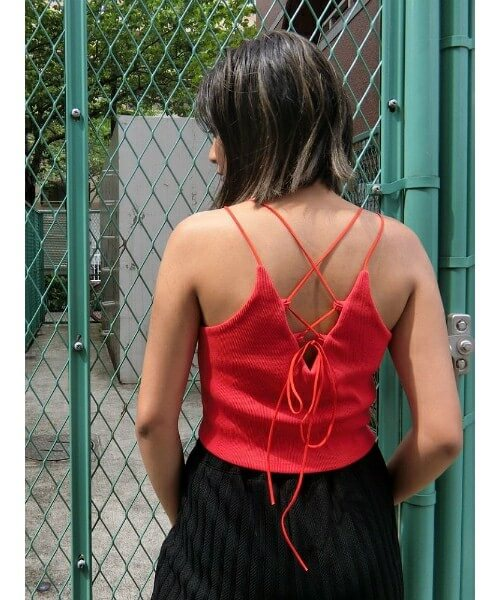 赤い背中開きキャミを着て後ろを向いている女性