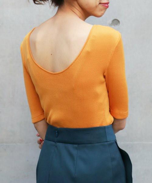 オレンジの背中開きリブトップスをきている女性