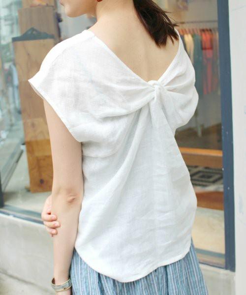 白の背中開きTシャツをきて右手を左手にかけている女性