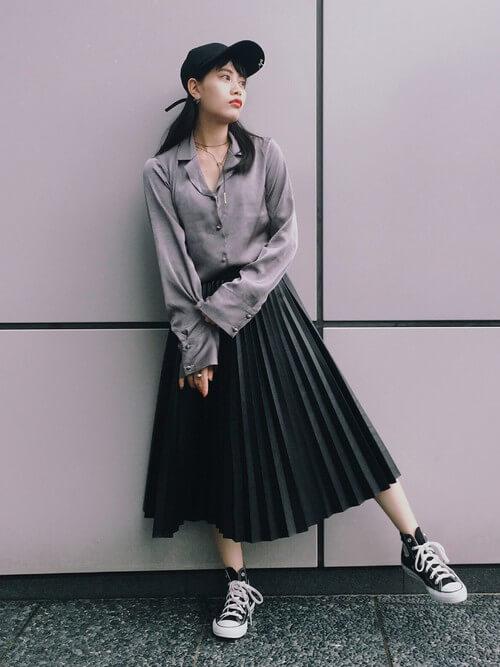 グレーのとろみシャツに黒いプリーツスカートを合わせて黒いスニーカーを履いた女性