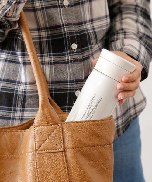 白の水筒をバッグに入れようとしてる女性