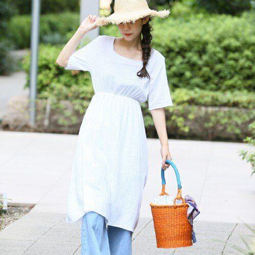 白いコットンワンピースにデニムパンツを履いた女性