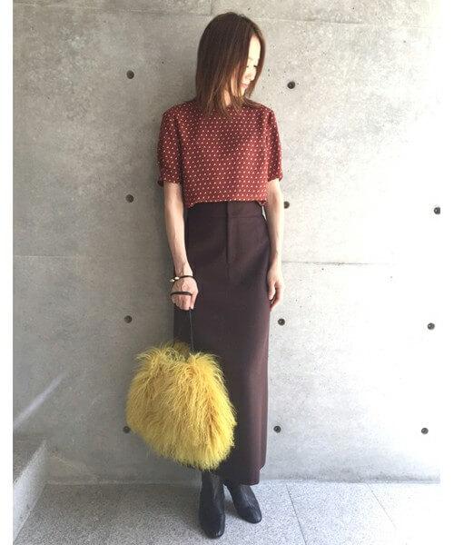 イエローのファーバッグにテラコッタカラーのトップスとタイトスカートの女性