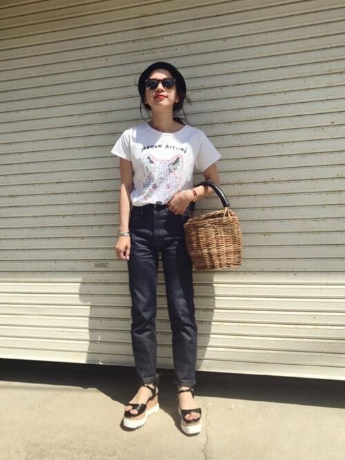 キツネの白Tシャツ×デニムにかごバッグを持った女性
