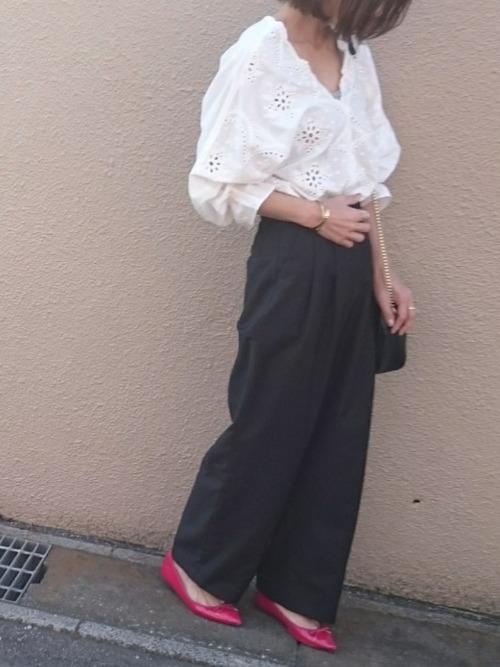 白のスカラップブラウスにネイビーのワイドパンツを履いた女性