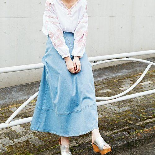白ブラウスに水色スカートを履いている女性