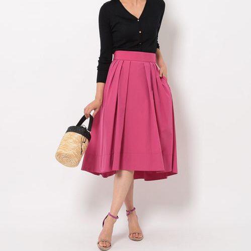 黒トップスにピンクスカートを履いた女性